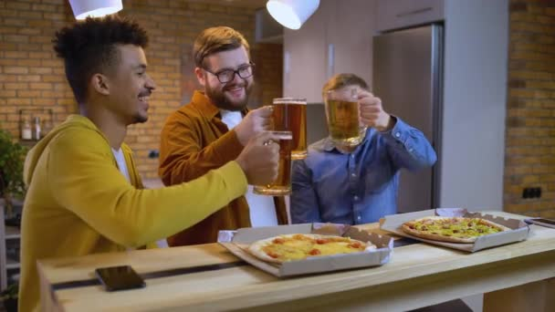 Three happy friends clinking glasses with beer, male party at home, friendship