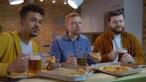 Barátok focimeccset néznek otthon, pizzát esznek és sört isznak, pihennek.