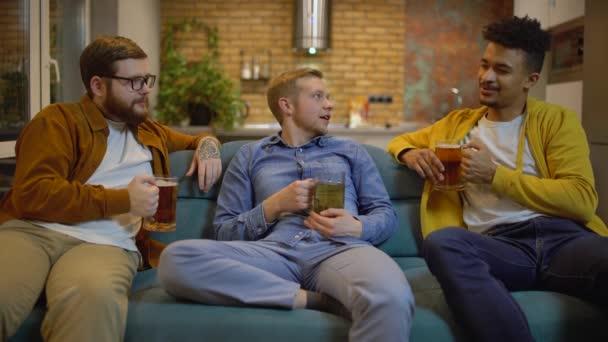 Boldog fiatal férfiak söröznek, beszélgetnek a kanapén, a barátok élvezik a kommunikációt