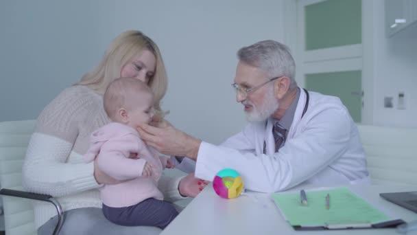 Milý pediatr vyšetřuje roztomilé dítě, poradí se s mladou matkou v nemocnici