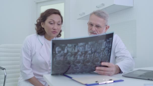 Female intern and senior doctor looking at x-ray image, discussing diagnosis
