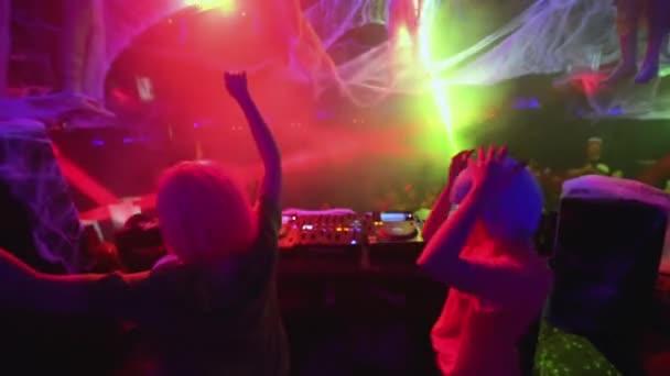 Female disc jockeys working at mixer in night club, people dancing at festival