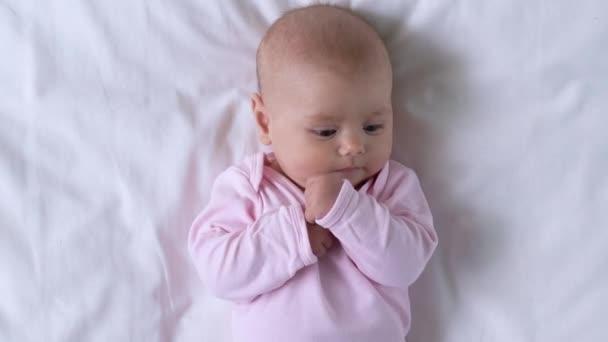 Imádnivaló csecsemő baba feküdt az ágyon, hogy apró kéz a szájban, kisgyermekkor