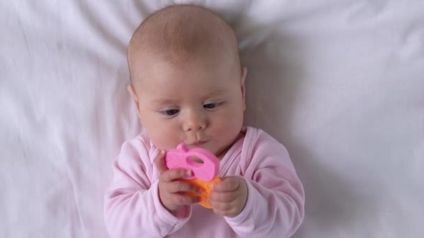 Cute baby chewing colorful teething toy to relieve pain, early development