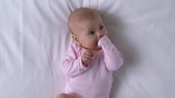Vtipná holčička, co si strká ručičky do pusy, rozhlíží se, hravé nemluvně