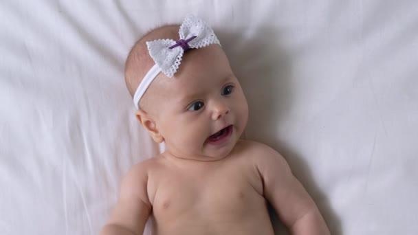 Liebenswertes kleines Mädchen, das auf dem Bett liegt, sich mit winzigen Armen bewegt und die Welt betrachtet