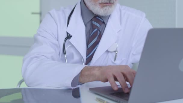 Surgeon looking at x-ray image, typing on laptop, entering results of analysis