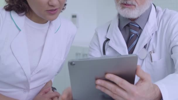 Two medical experts discussing diagnosis, looking at tablet images, teamwork