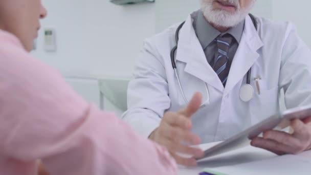 Arzt zeigt dem Patienten Testergebnisse per Tablet, Online-App und Konsultation