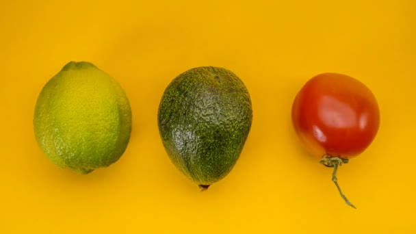 Avocado, lemons and tomato rolling on a yellow background, stop motion animation, 4k