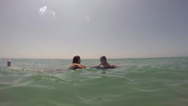 Girl and mother swimming in sea