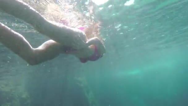 woman in bikini swimming under water