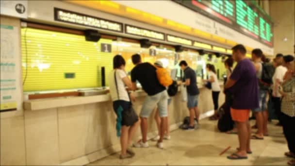 People buying tickets at train station