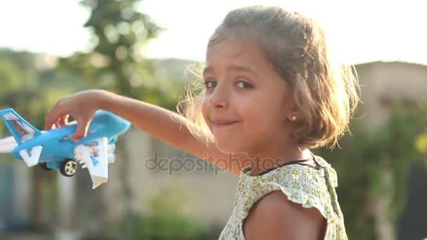 Dívka si hraje s hračkou letadla