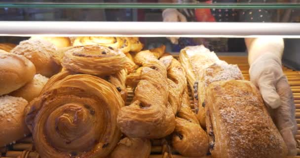 baker displaying pastries products on bakery window for customer choice. Buns, cakes, cookies, muffins. Varied selection of delicatessen homemade fresh sweet dessert.