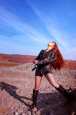 Girl with guitar in leather jacket