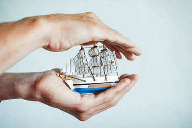 toy ship in hands