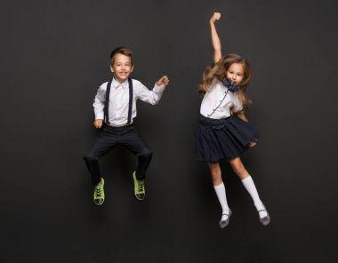 kids dressed in school uniform jumping