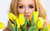 Fotografie Beautiful blonde girl in pink dress with yellow flowers tulips in hands