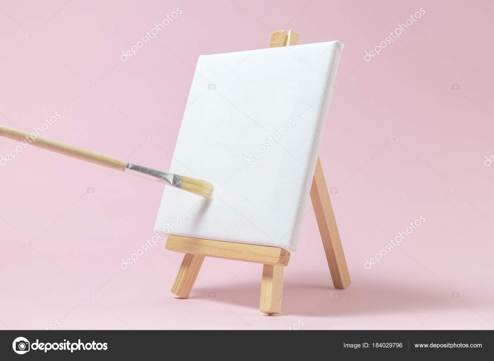 blank art board canvas with wooden stand miniature and paintbrush on