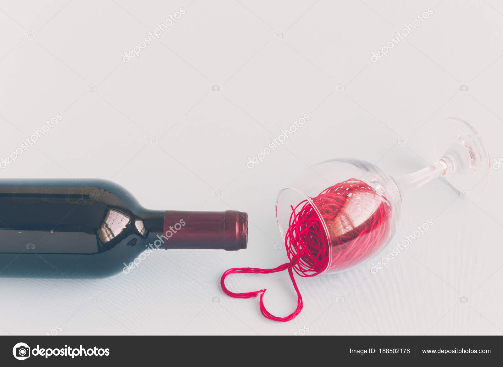 bottle and red wine spilled from wineglass minimalistic concept