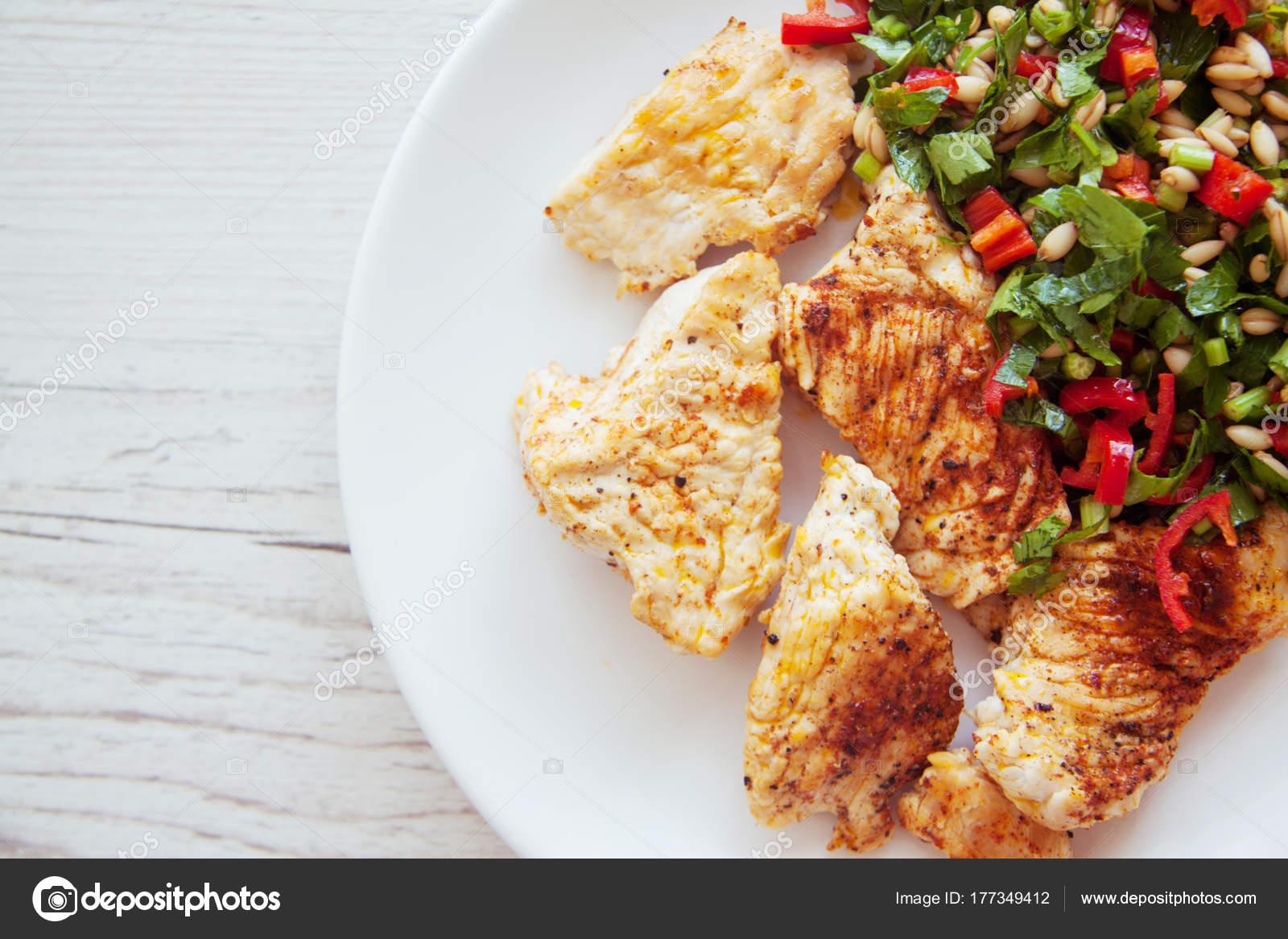 côtelettes de poulet et salade verte sur plaque — photographie
