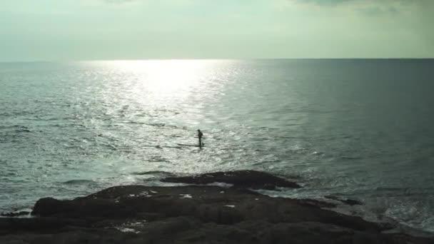 Mann steht auf dem Paddelbrett auf dem Meer