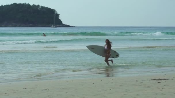 Young Woman Carrying A Surfboard Across The Beach