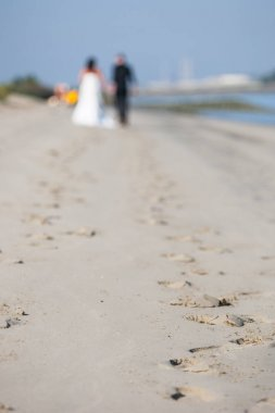 Unrecognizable newlywed couple walking on a beach