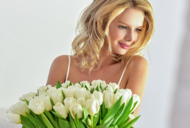 Beautiful young blond woman with tulip bouquet