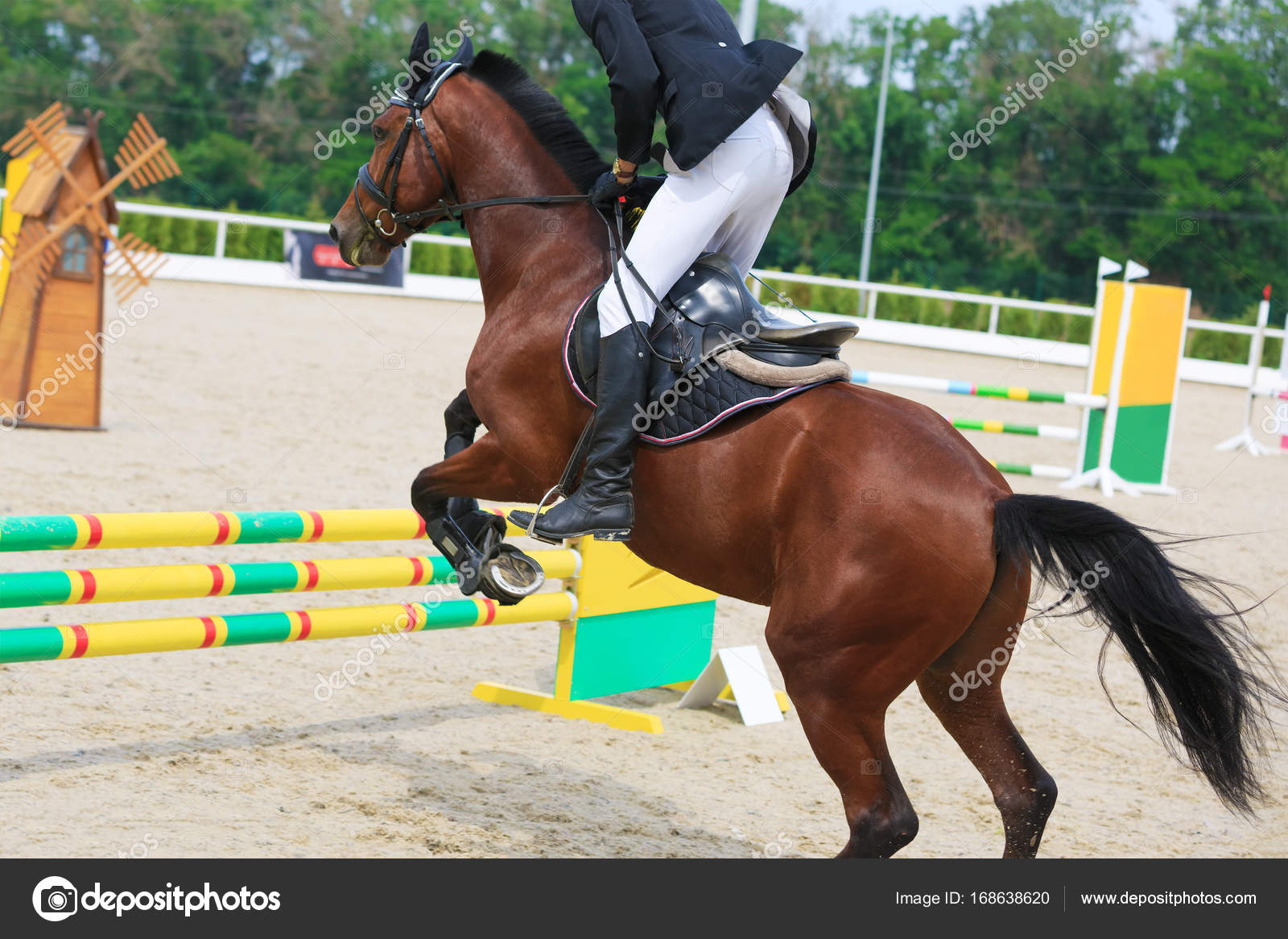 Chestnut Horse Jumping Rider On A Chestnut Horse Jumps Over A Barrier In Jumping Competition Stock Photo C Ovbelov 168638620