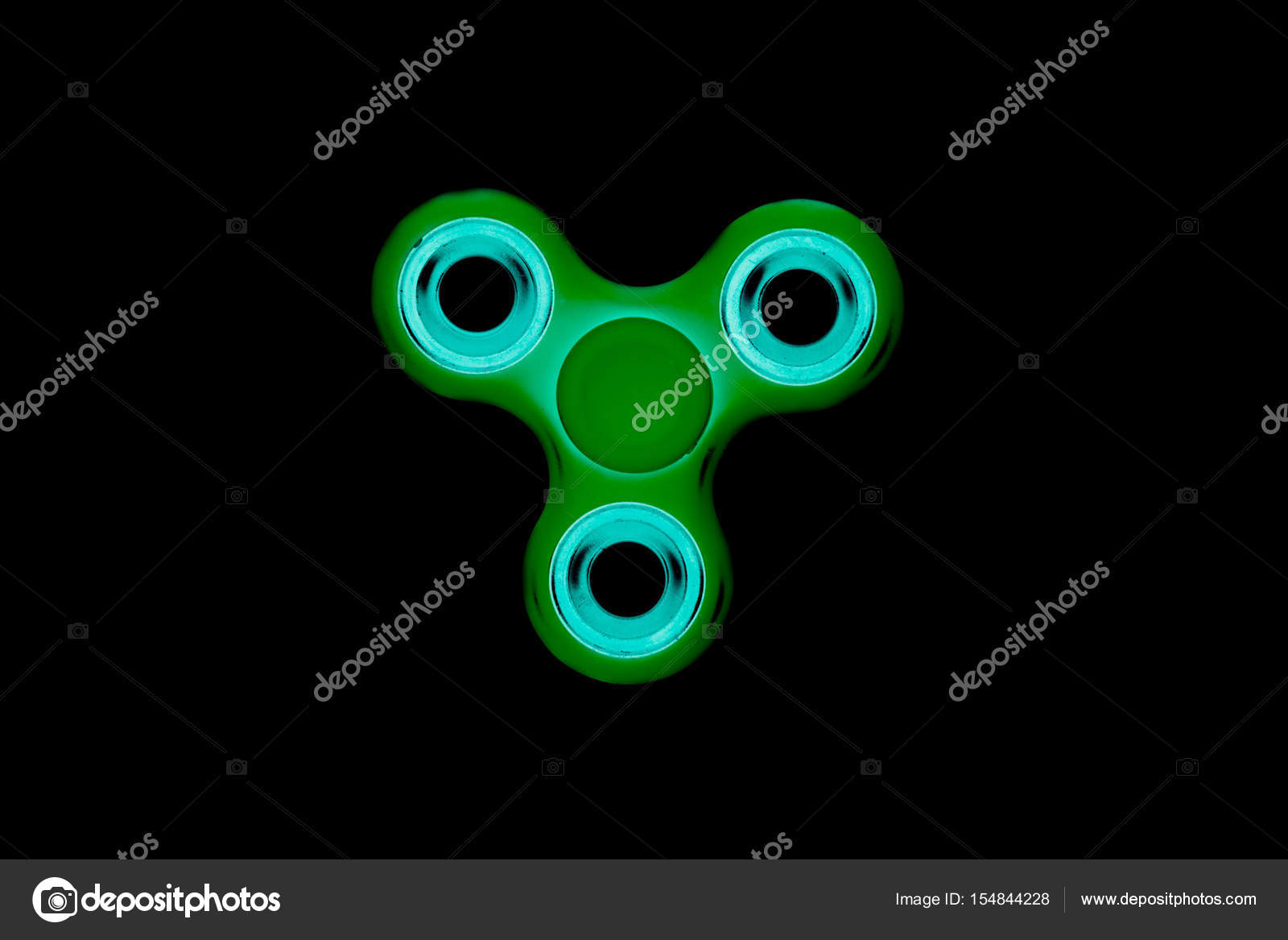 Green Fidget Spinner In Black Isolated Background For Stress Release During Work Stock Photo
