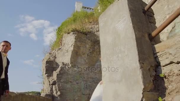 Mladí svatební pár pózuje na starých kamenných schodech. Starožitný hrad 4k