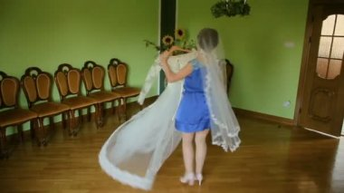 Young attractive woman choosing wedding dress, posing and trying on