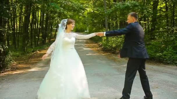 glücklicher Bräutigam und schöne Braut im weißen Kleid tanzen im grünen Wald