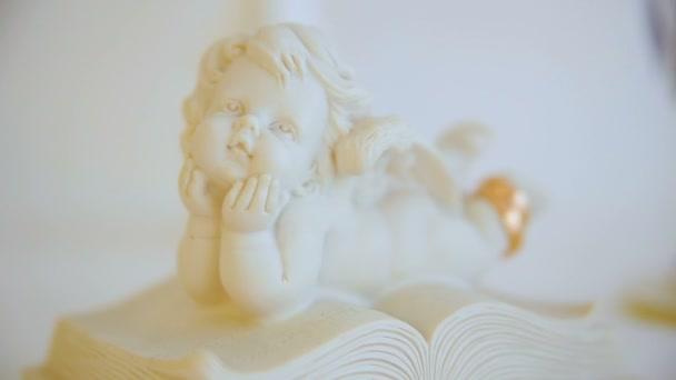 dva snubní zlaté prsteny. soška anděl postava. Angel na knihu. closeup