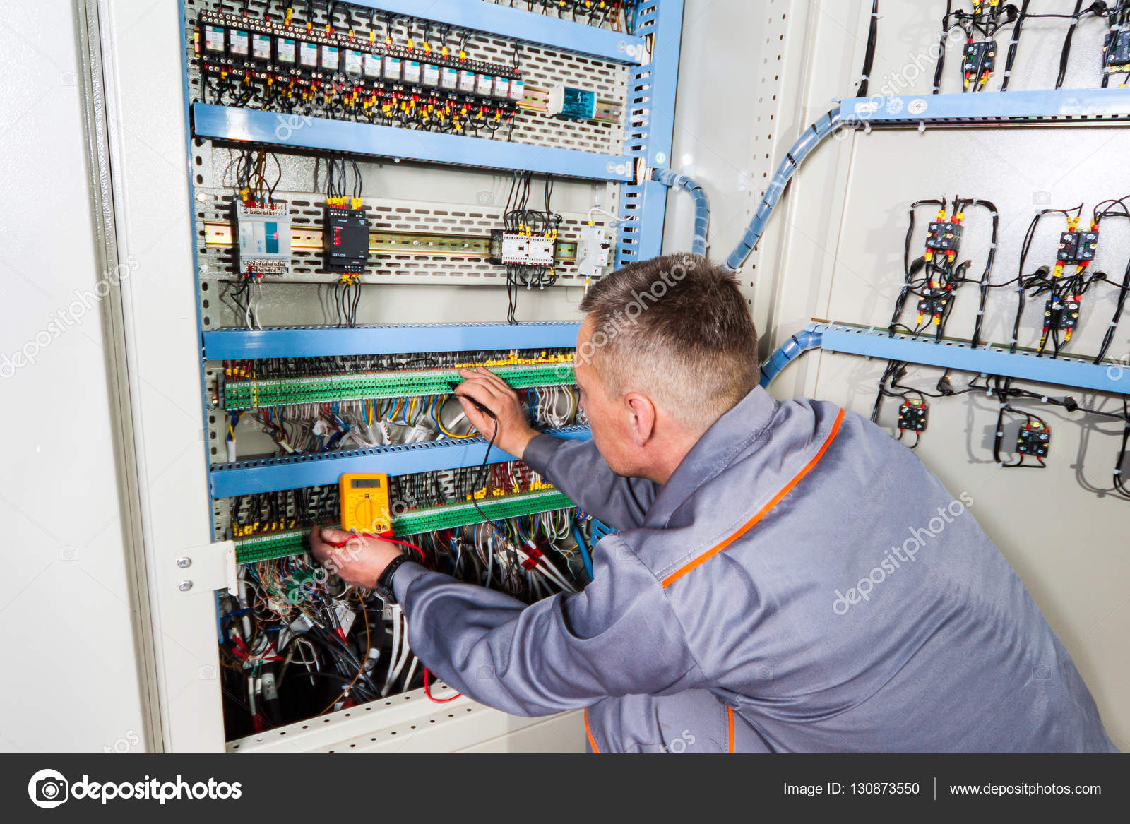 electrician testing industrial machine, electrician builder engineer  screwing equipment in fuse box, male electrician ⬇ stock photo, image by ©  bondvit #130873550  depositphotos