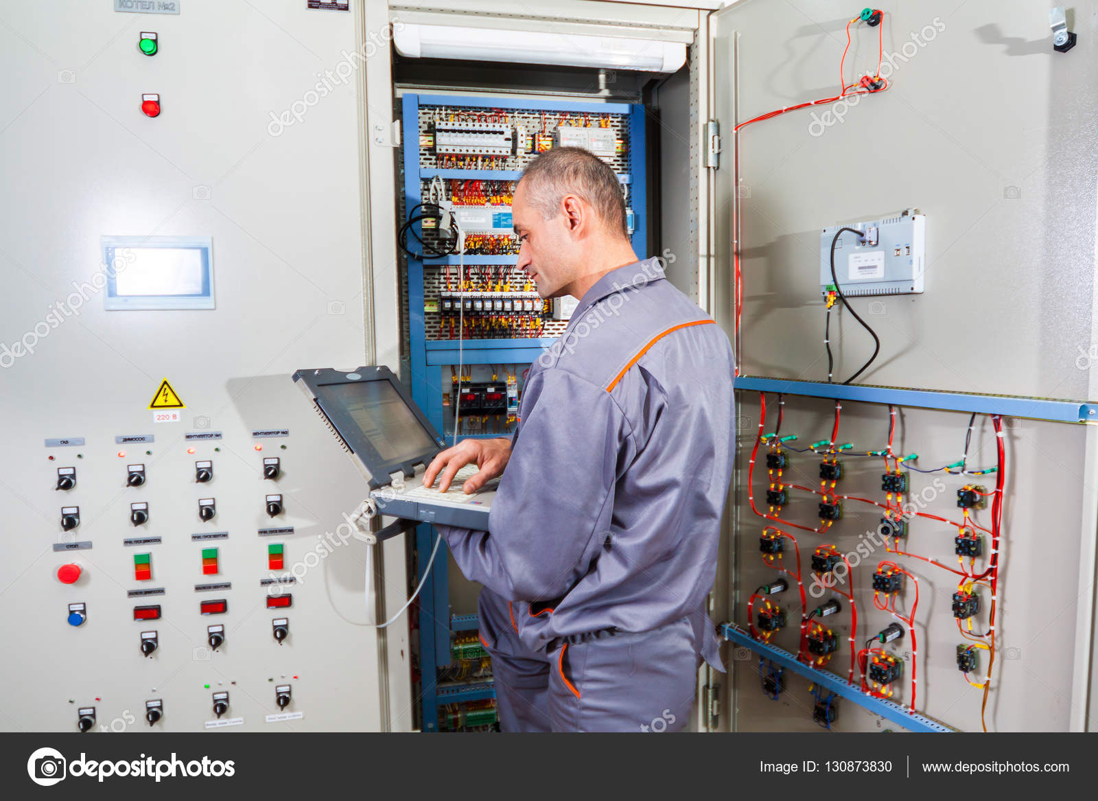 electrician testing industrial machine, electrician builder engineer  screwing equipment in fuse box, male electrician