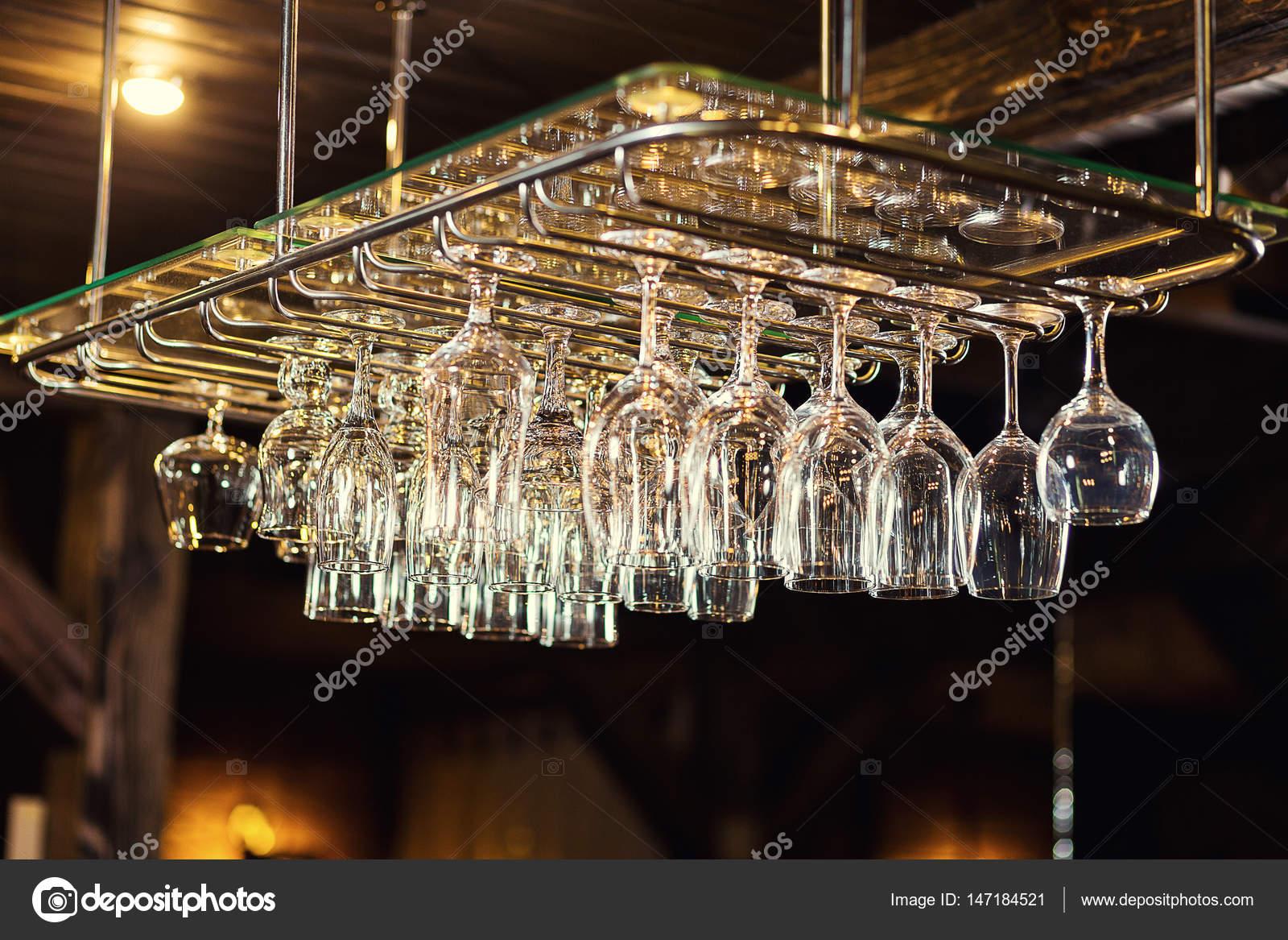 https://st3.depositphotos.com/8000700/14718/i/1600/depositphotos_147184521-stock-photo-glasses-hanging-over-a-bar.jpg