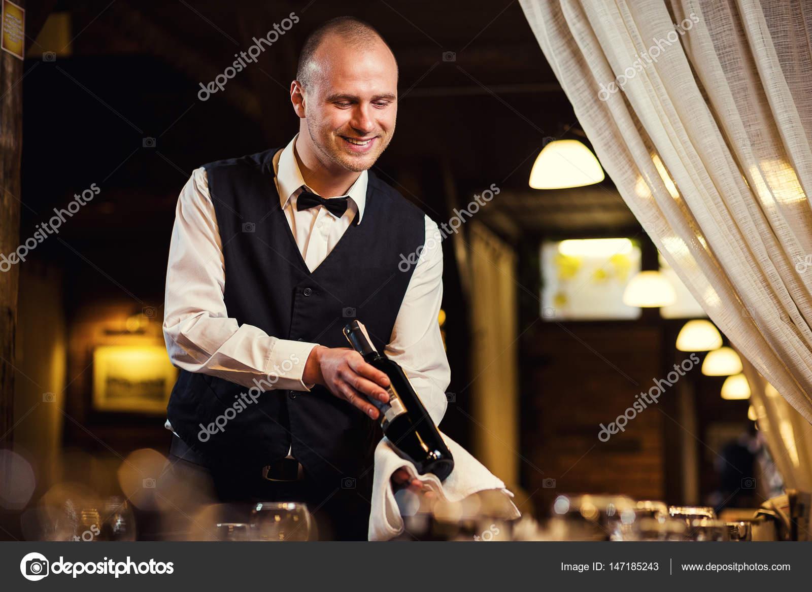 El camarero ofrece vino, camarero de uniforme esperando una orden ...
