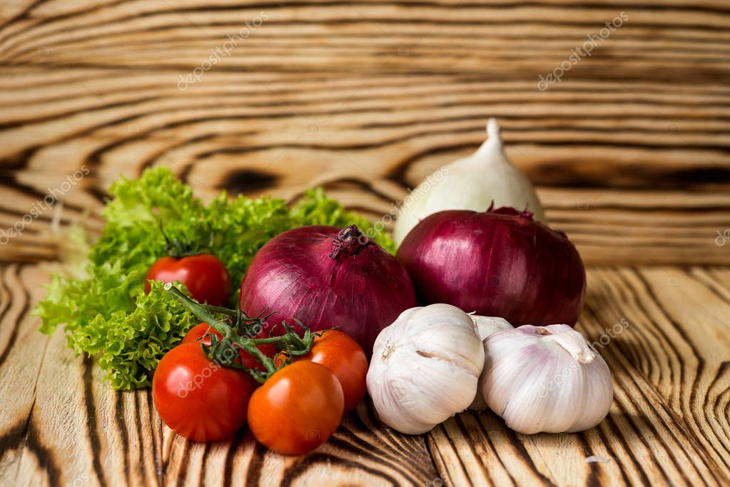 Composition with assorted raw organic vegetables such as tomatoes, salad, herbs, onions and garlic. Detox diet