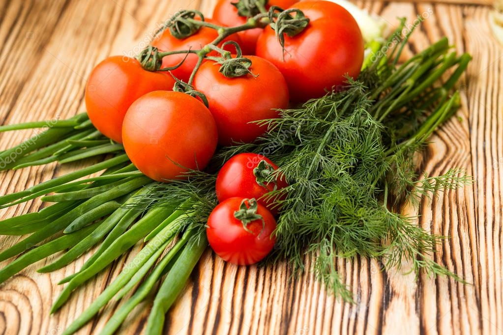 Composition with assorted raw organic vegetables such as tomatoes, herbs and onions. Detox diet