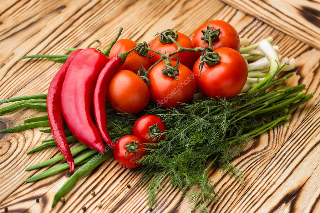 Composition with assorted raw organic vegetables such as tomatoes, sweet peppers, herbs and onions. Detox diet