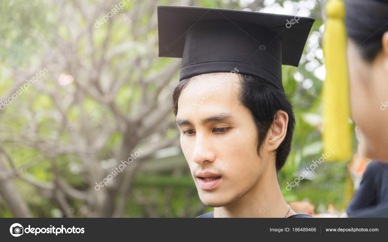 29d76d928 Hombre estudiante sonrisas y sentirse feliz en tapa y vestidos de la  graduación — Foto de