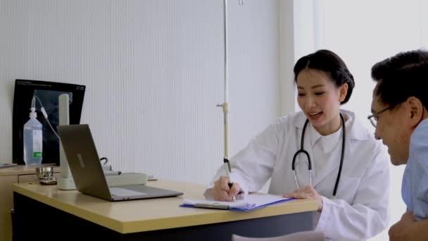 Asiatische Ärztin berät eine ältere Seniorin, die im Rollstuhl im Patientenzimmer sitzt, Hintergrund weißer Vorhang im Krankenhaus.