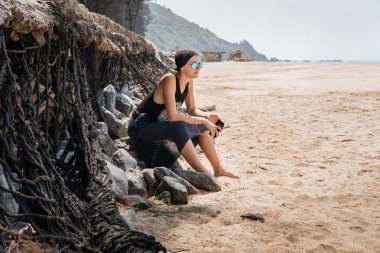 Young stylish girl with glasses bald sport sitting on stones on a sandy beach and listening to music on headphones