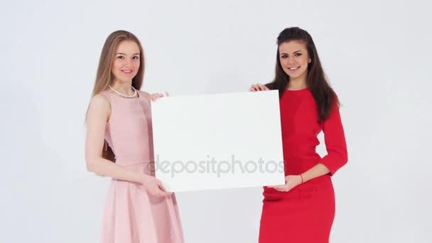 Dva usmívající se atraktivní dívky při pohledu na fotoaparát drží bílý prázdný nápis