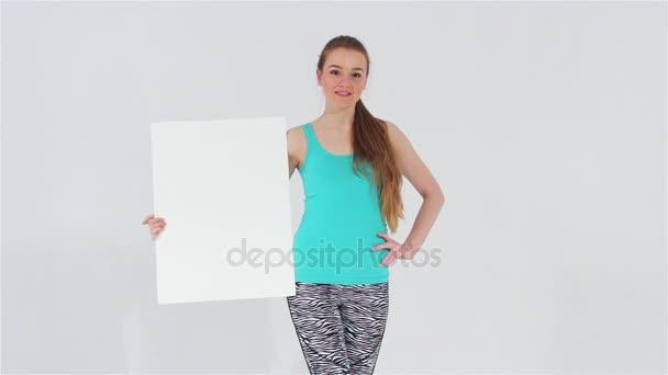 S úsměvem atraktivní dívka v autě sportu při pohledu na fotoaparát drží bílý prázdný nápis