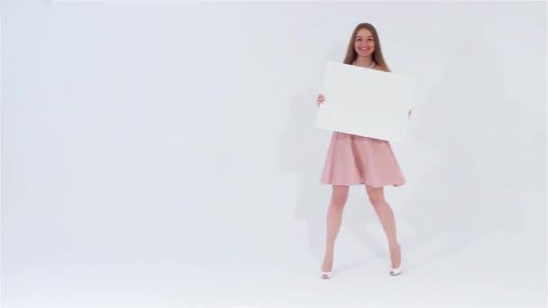 Usmívající se atraktivní dívka v růžových šatech chůzi a při pohledu na fotoaparát drží bílý prázdný nápis