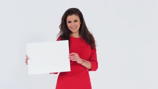 Usmívající se krásná dívka s korálové šaty při pohledu na fotoaparát a drží prázdný bílý nápis